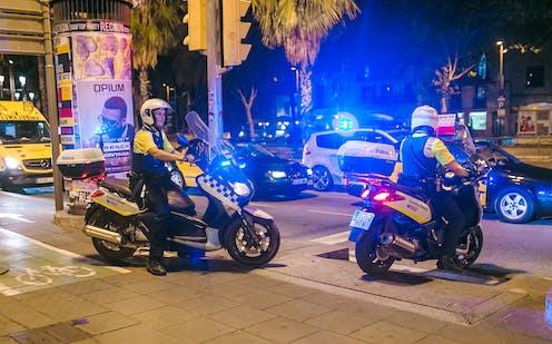 Policías locales de Barcelona en sendas motos, de noche, con las luces encendidas.