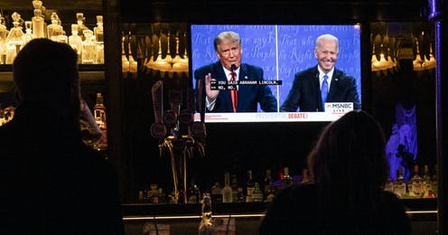 People in a bar watching Trump and Biden on television.
