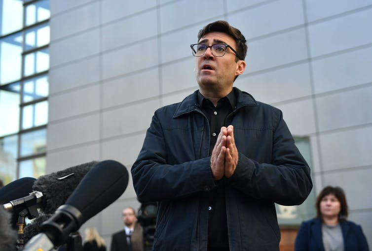 Andy Burnham addressing a public audience outside.