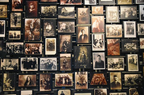 Wall of photographs showing Jewish people in the 1940s in a family setting.