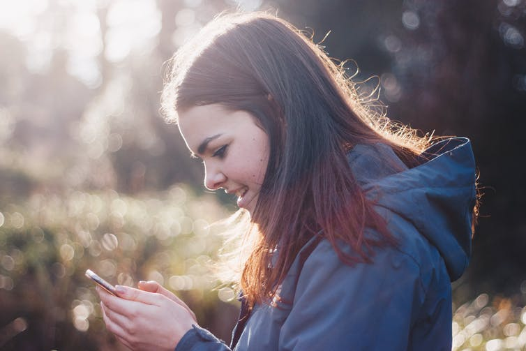 A teenaged girl looks at her phone outdoors.