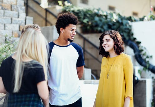 Three young people chat outdoors.