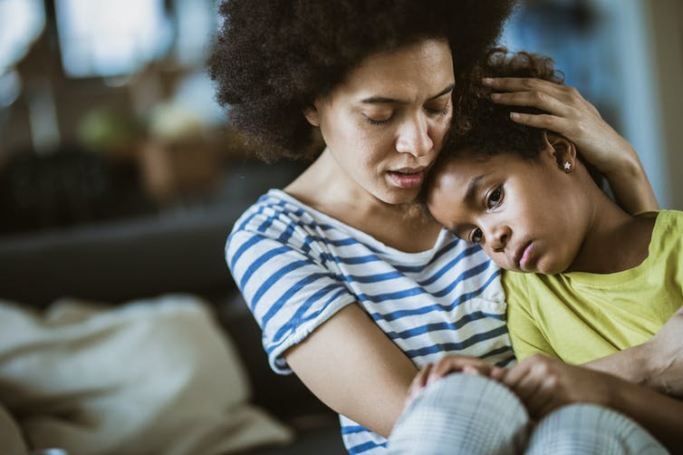 Young black mother comforting sad school age daughter at home.
