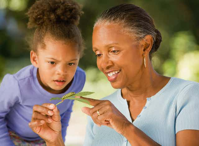 A young girl and a woman look at a caterpillar on a leaf.