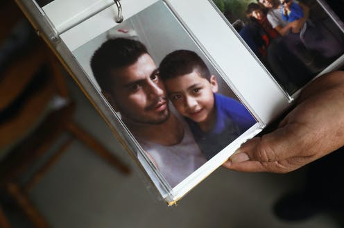 Photo album held open showing a picture of a young man and little boy