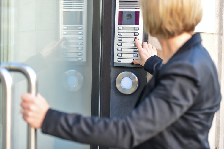 A woman using an intercom and pulling open a door
