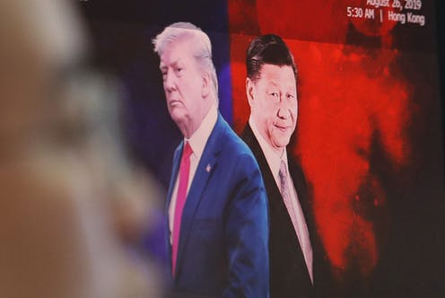 A computer screen shows images of Chinese President Xi Jinping and U.S. President Donald Trump as a currency trader works at the foreign exchange dealing room of the KEB Hana Bank headquarters in Seoul.