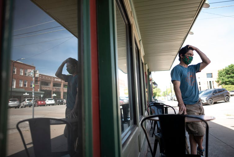 A cafe owner wears a protective face mask in Stillwater, Oklahoma.