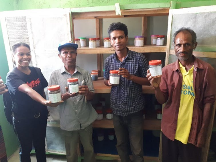 A woman and two men hold jars of seeds