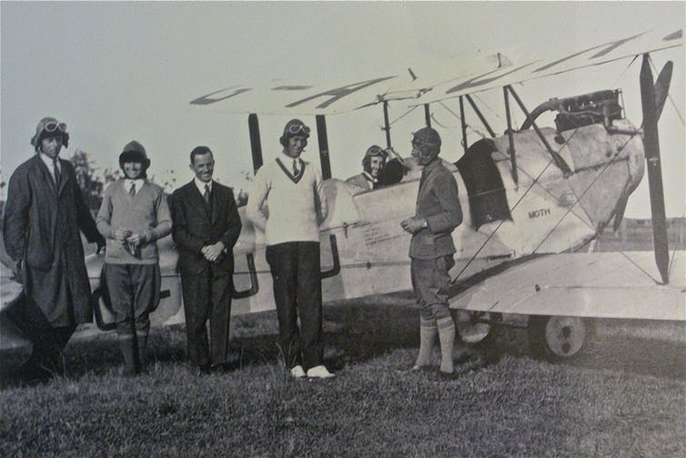 Millicent Bryant with a plane and other aviators.
