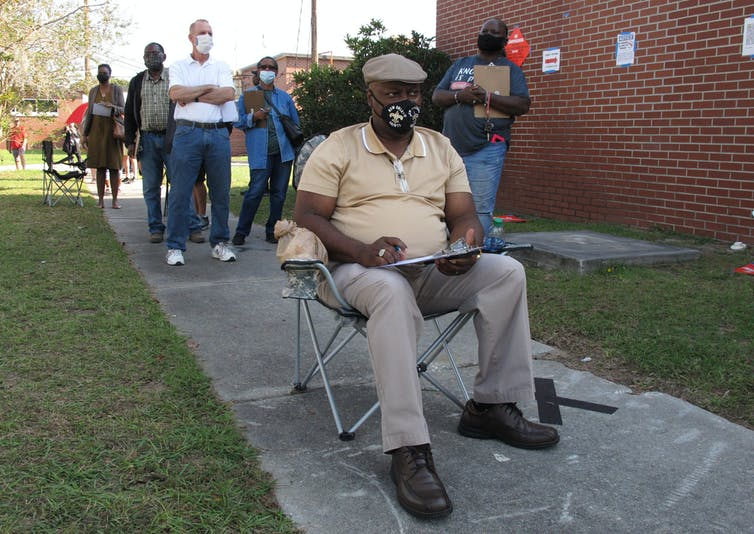 A man sits in a folding chair, waiting to vote in Savannah, Georgia