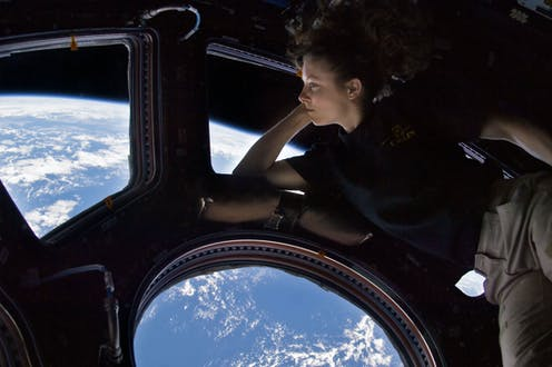 A woman floats in front of windows showing a view of Earth far below.