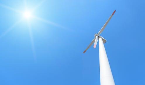 wind turbine against blue sky and sun