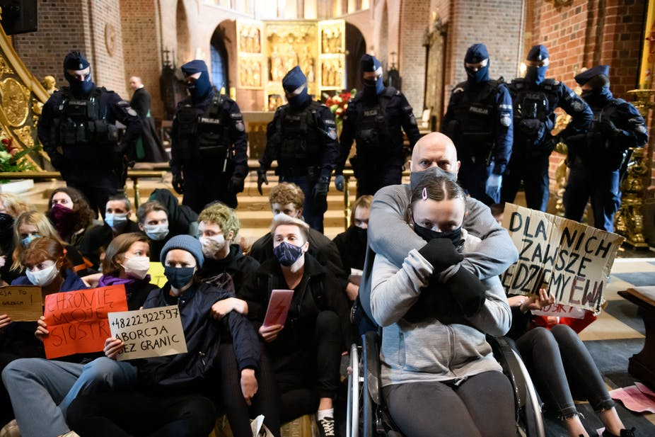 Protestors wearing masks sit in front of advancing police.