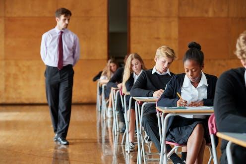 Teenage students writing an exam with a teacher invigilating.