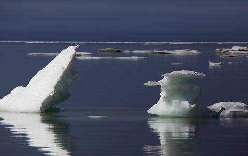 Ice floes jut at angles out of mostly empty seawater.