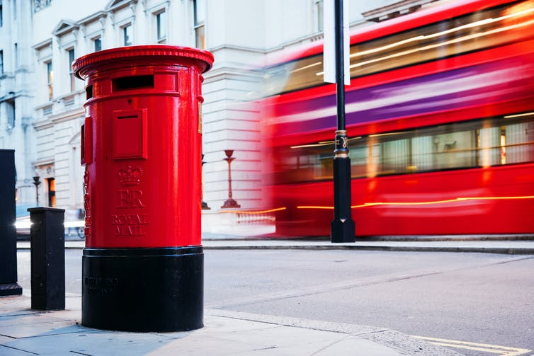 Red post box on street with red London bus behind.