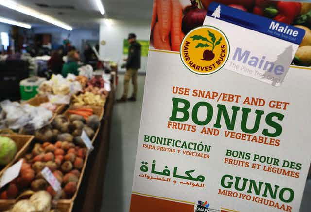 Fruits and vegetables in  boxes next to a sign in multiple languages.