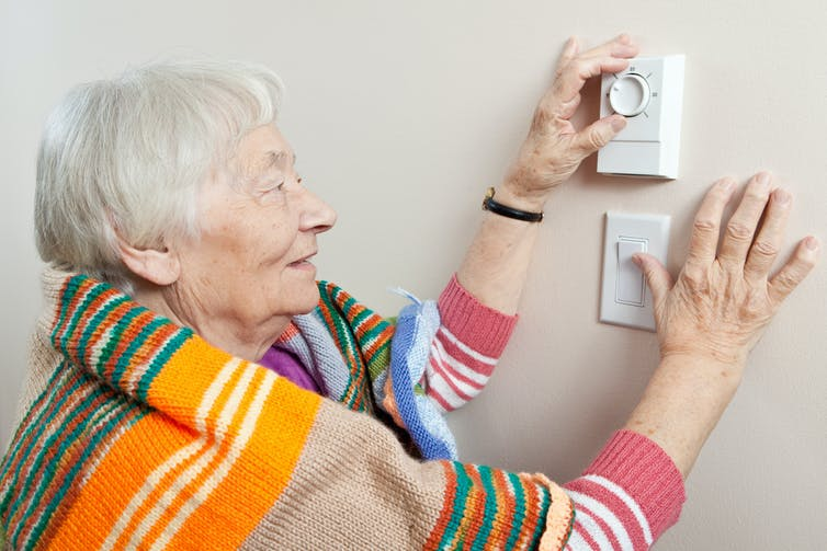 Elderly woman wrapped in blanket adjusting thermostat