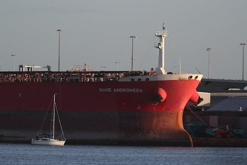 A docked red tanker ship.