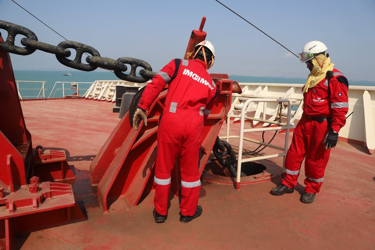 Two people in high visibility suits work on a ship deck.