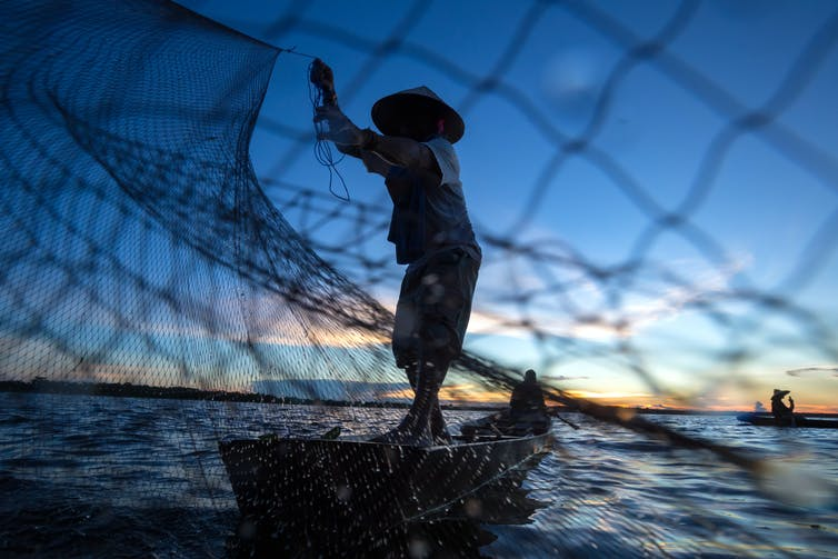 A fisher on a wooden boat casts a net into tropical water at dusk.