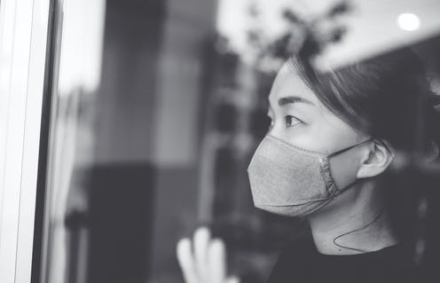 A woman wearing a mask looks out of a window.