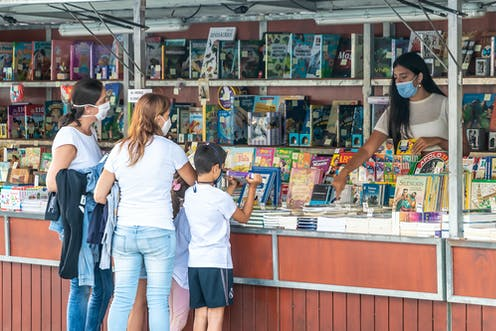 Tres personas con mascarilla ante un puesto de la feria del libro de Punta Umbría (Huelva)