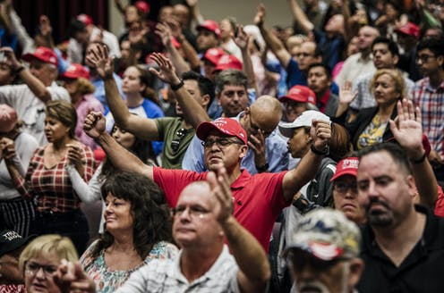 "Attendees pray together before President Donald Trump addresses the crowd at the King Jesus International Ministry during a ""Evangelicals for Trump"" rally in Miami."