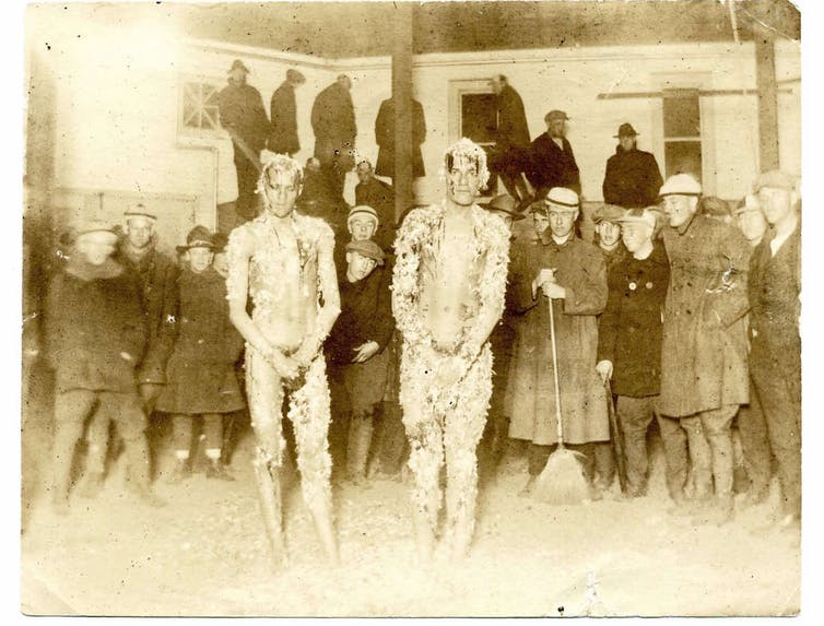 Two African American men stand together doused in tar and feathers among a crowd of white students .