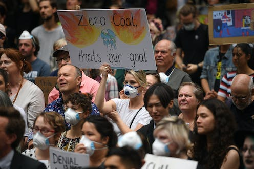"A protestor holds up a sign saying ""zero coal that's our goal"""