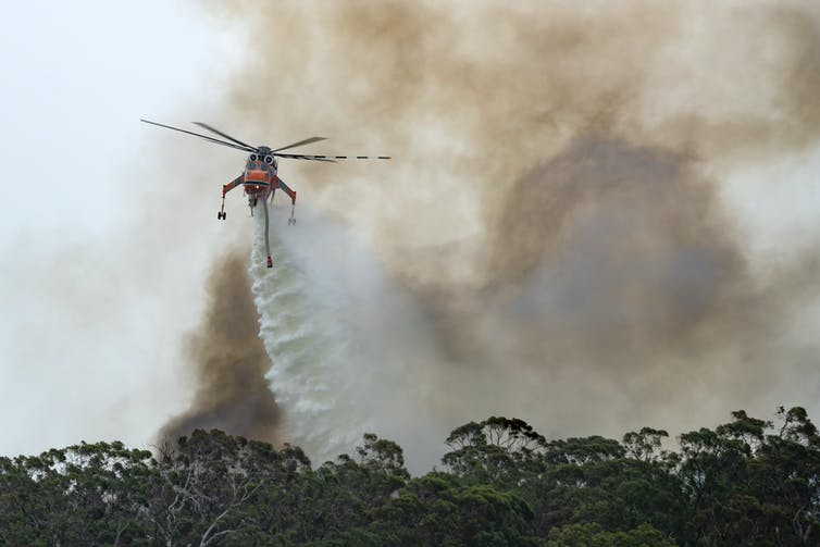Helicopter dumping water over bushfires