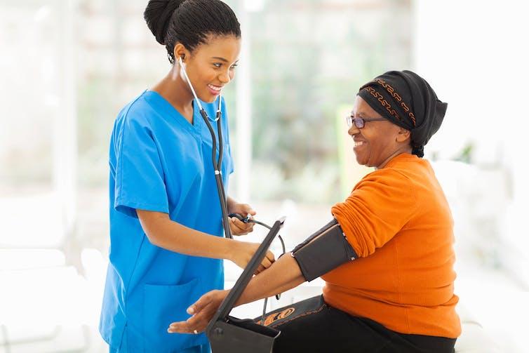 A health worker taking an elderly patient's blood pressure