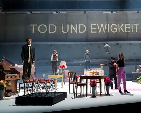 Production image, cast on stage looks to audience