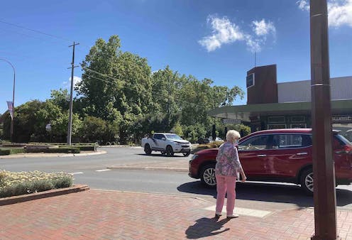 Older woman waits for traffic as she tries to cross the road