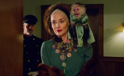 Expensively dressed woman with monkey on her shoulder.
