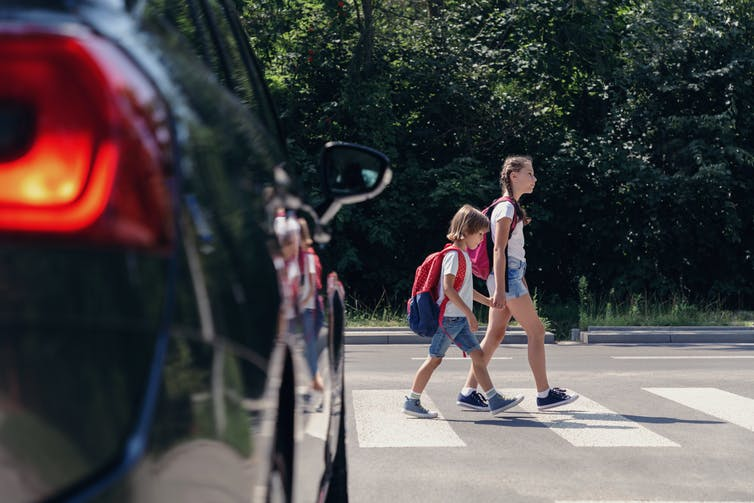 Children cross the road in front of a car.