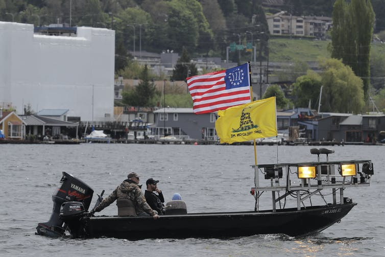 A boat flies the Gadsden 'Don't tread on me' flag and a Three Percenters flag.