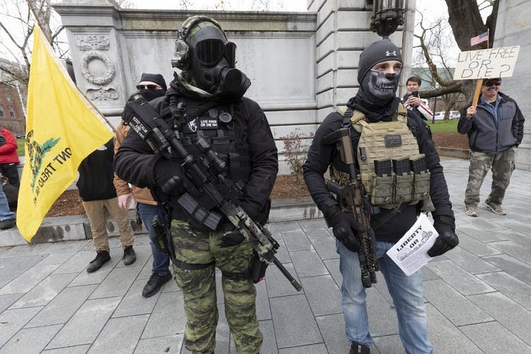 People wearing camouflage and carrying weapons