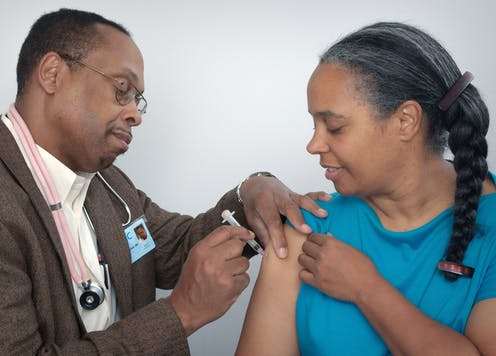 A man wearing a stethoscope gives a woman a shot in her upper arm.