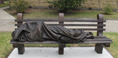 a bronze sculpture is shown prone on a park bench.