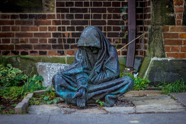 a bronze sculpture depicts a person wrapped in a blanket with an hand stretch out palm turned up as if asking for food or money.