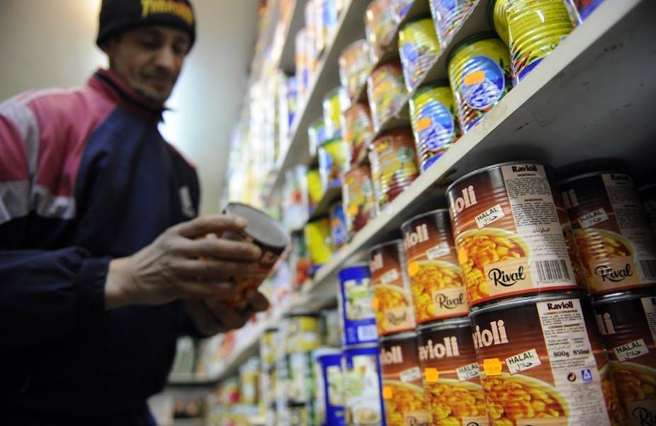 Un commerçant range une boite de conserve de nourriture halal dans un rayon