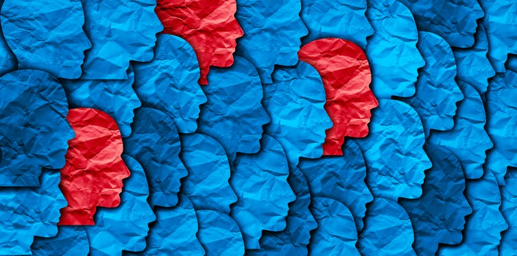 A graphic showing a collage of blue paper faces with a few isolated red faces