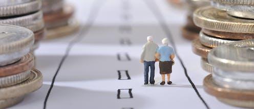 Una pareja de muñecos de ancianos camina de espaldas entre monedas apiladas en lo márgenes de un camino dibujado en el suelo.