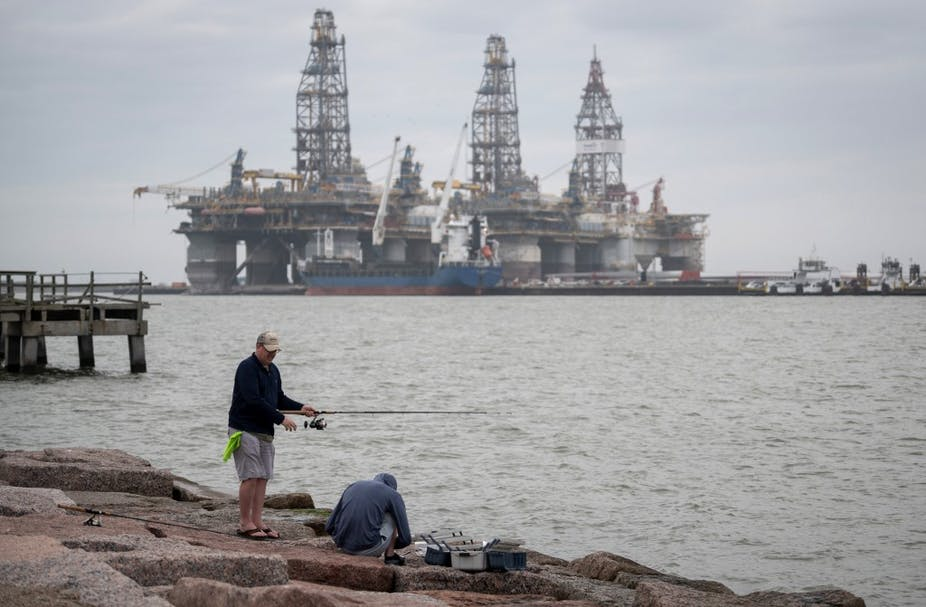 Fishermen on the shore by decommissioned oil rigs in Port Aransas, Texas