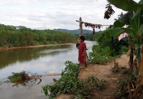 Tsimane children stand on a river bluff
