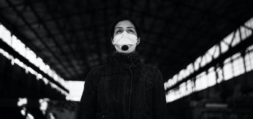 Foto en blanco y negro de una mujer con mascarilla dentro de una nave mirando al infinito.
