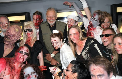 Zombies surround man in a green vest and a white beard.