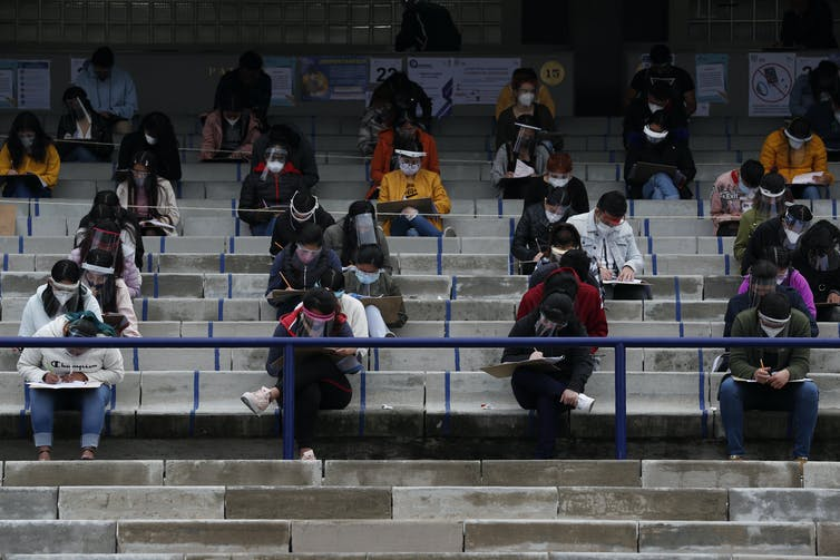 Students sit in an outdoor stadium writing entrance exams.